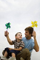 Little boy sitting on father´s lap, both holding pinwheels