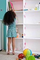 Little girl reaching for book on shelf in bedroom, rear view