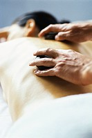 Lastone therapy, stones being positioned on patient´s bare back