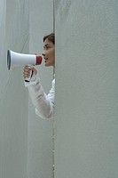 Woman speaking into megaphone, side view