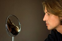 Man looking at self in cosmetic mirror