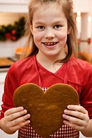 Smiling girl holding a ginger bread heart Sweden.