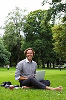 A man with a laptop in a park Sweden.