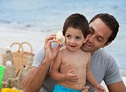 Hispanic man holding seashell to son´s ear