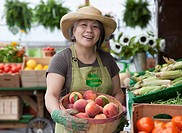 Japanese woman holding basket of peaches at farmer´s market