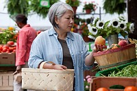 Japanese woman looking at fruit at farmer´s market