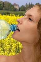 Woman drinking water and rape field