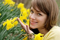 Young woman smells on a daffodil