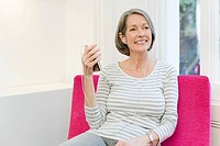 Mature woman listening to mp3 player (thumbnail)