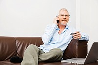 Mature man using telephone banking