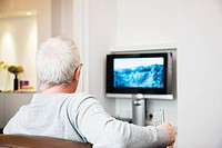 Mature man watching television