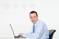 Office worker with laptop and wall clocks