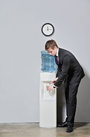 Businessman pouring water into a glass from a water cooler