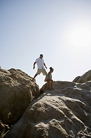 Father and daughter climbing rocks