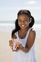 Girl holding a shell on beach
