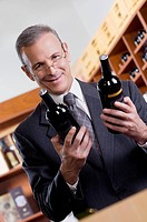 Businessman holding wine bottles