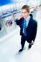 Businessman talking on a mobile phone in a laundromat