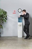 Businessman leaning on a water cooler and drinking water