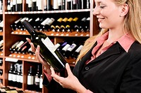 Businesswoman choosing a wine bottle
