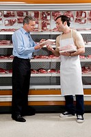 Sales clerk assisting a customer choosing meat in a supermarket
