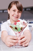 Girl holding a glass of ice cream and smiling