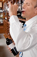 Businessman tasting wine in a cellar