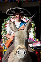 Man riding a stuffed donkey and holding a gun, Olvera Street, Los Angeles, California, USA