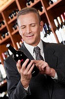 Businessman reading the label on a wine bottle