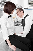 Male and a female waiters smiling at each other