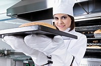 Female chef holding a bun in a tray