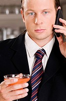 Businessman talking on a mobile phone and holding a cocktail glass
