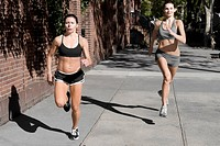 Two women jogging in a street