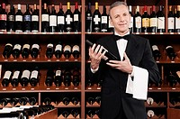 Businessman holding a wine bottle in a bar