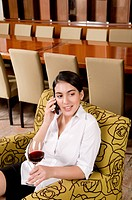 Businesswoman talking on a mobile phone and holding a glass of wine