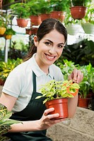 Woman holding a potted plant in a greenhouse