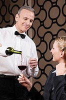 Waiter pouring red wine into a wine glass held by a woman