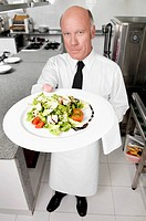 Waiter holding vegetable salad in plate