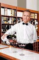 Waiter pouring red wine into wine glasses in a bar