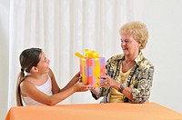 The girl passes the present to the grandma