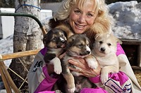 Sled dog musher, Dee Dee Jonrowe, poses with several puppies at her home in Willow, Alaska