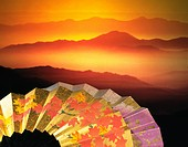Folding fan in front of mountain range