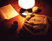 Knitting next to pattern book with coffee cup and lamp