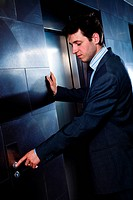 Businessman calling elevator