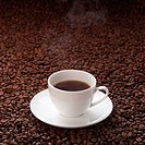 Steaming coffee cup on coffee beans