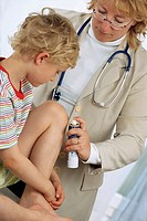 5 year old boy and doctor spraying clean a bruise