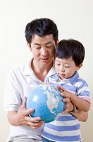 Family, father and son holding a globe