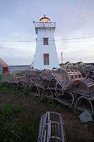 Lobster traps stacked in front of a light house in Prince Edward Island, Canada
