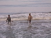 Men walking into shore from Arabian Sea