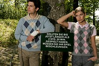 Young couple next to sign on golf course