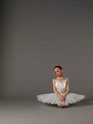 Girl in white tutu kneeling.